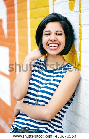 Portrait of beautiful laughing young hipster brunette latin hispanic girl woman with short hair bob, in blue jeans, striped tshirt, leaning on brick wall in city looking in camera - stock photo