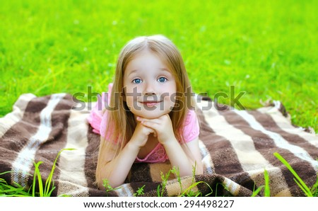 Portrait of beautiful little girl child lying resting on the grass plaid - stock photo