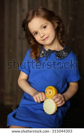 Portrait of beautiful little girl, holding a vintage toy - tilting doll . Dark wooden  background. Studio shot - stock photo