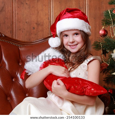 Portrait of beautiful little girl holding red boot gift on Christmas time on Holiday theme/Portrait of a little girl wearing Santa Claus hat with christmas stocking - stock photo