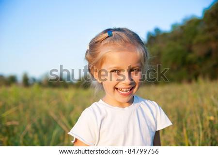 portrait of beautiful little girl in a meadow - stock photo