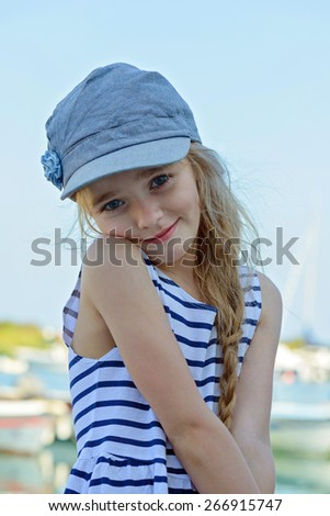 Portrait of beautiful little girl in denim cap and striped clothes posing outdoors - stock photo