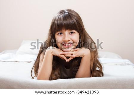Portrait of beautiful little girl lying on bed in pajamas.Beautiful little girl lying on bed - stock photo
