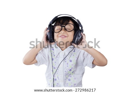 Portrait of beautiful little girl wearing a glasses while listening music with headphones - stock photo