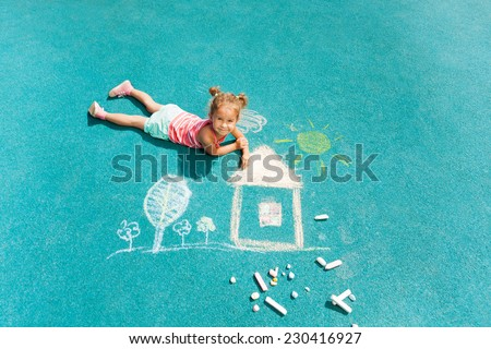 Portrait of beautiful little girl with chalk laying and drawing on rubber playground surface looking up - stock photo