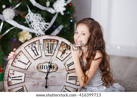 Portrait of Beautiful little girl with long curly hair in silver dress with a big clock waiting for the new year. New year preparation - stock photo