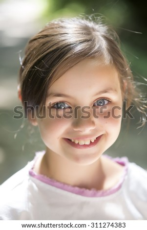 Portrait of beautiful little smiling girl with brunette hair and blue eyes in white blouse looking forward standing sunny day outdoor on natural background closeup, vertical picture - stock photo