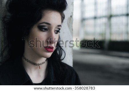 Portrait of beautiful lonely and sad goth girl outdoor in autumn. - stock photo
