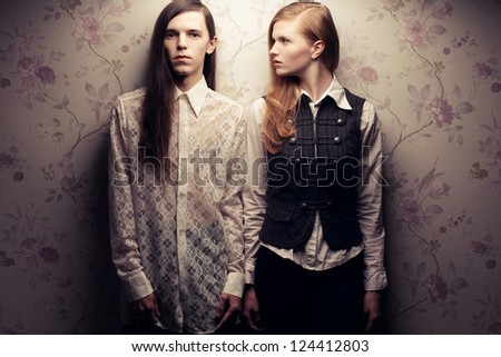 Portrait of beautiful long haired people in vintage style: handsome boy with brown hair and gorgeous red-haired girl posing together. Studio shot. - stock photo