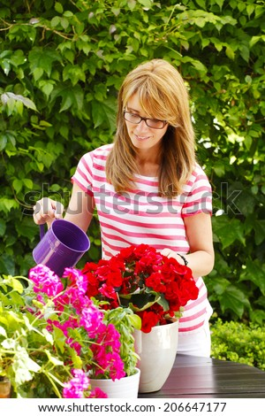 Portrait of beautiful mature florist standing. Small business.  - stock photo