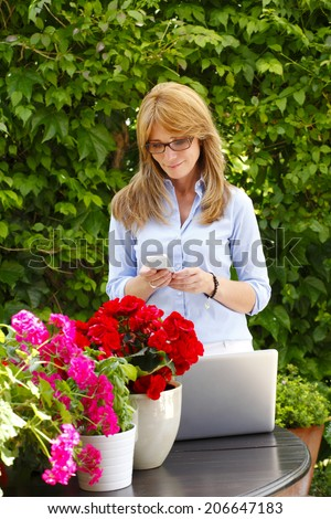 Portrait of beautiful mature florist with mobile, standing. Small business.  - stock photo