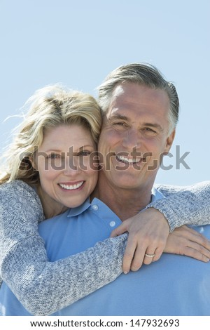 Portrait of beautiful mature woman embracing man from behind against clear sky - stock photo