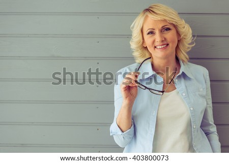 Portrait of beautiful mature woman holding eyeglasses, looking at camera and smiling, standing against gray background - stock photo