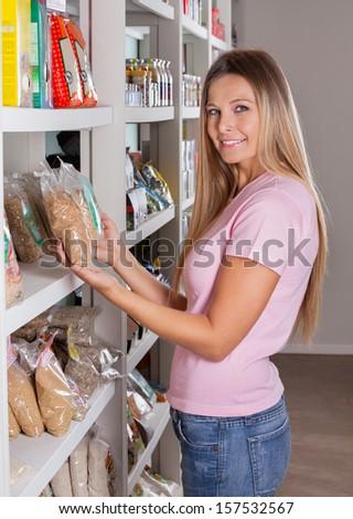 Portrait of beautiful mid adult woman choosing groceries in supermarket - stock photo
