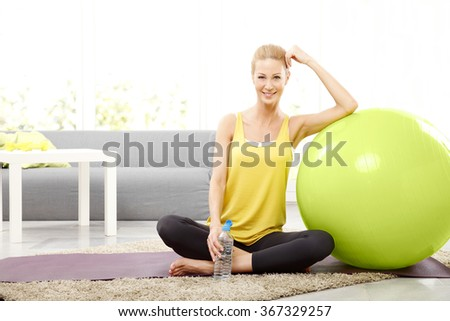 Portrait of beautiful middle age woman drinking a bottle of water while relaxing after fitness workout at home.  - stock photo