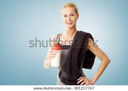Portrait of beautiful middle age woman holding in her hand a protein shaker bottle while standing at isolated background after fitness workout.  - stock photo