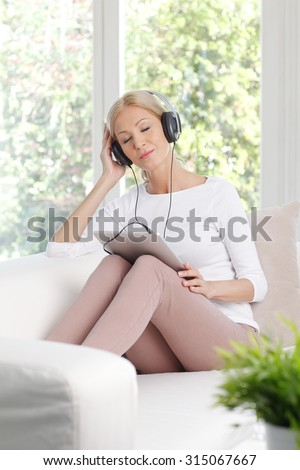Portrait of beautiful middle age woman listening music while sitting at home on the sofa. Smiling female with headphone using digital tablet and keeps her eyes closed while dreaming.  - stock photo