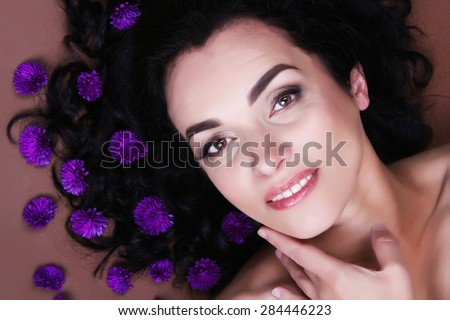 Portrait of beautiful middle aged woman with wild flowers - stock photo