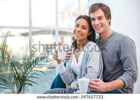 Portrait of beautiful mixed race young couple. Man and woman sitting near big window with cups of coffee at home. Couple feeling comfortable and smiling - stock photo