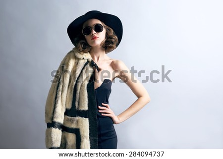 Portrait of beautiful model in fur coat, hat and sunglasses on gray background - stock photo
