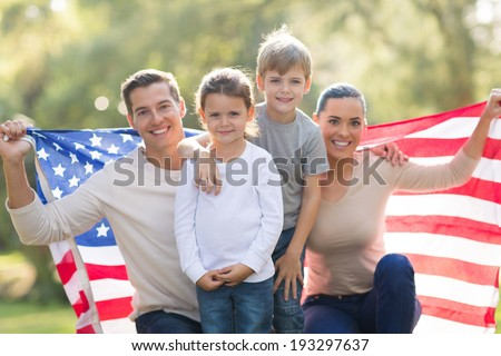 portrait of beautiful modern american family with USA flag outdoors - stock photo