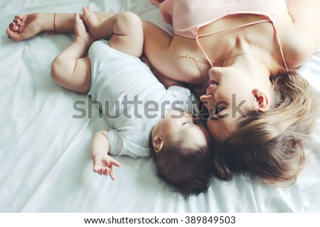 Portrait of beautiful mom playing with her 4 months old baby in bedroom, top view - stock photo