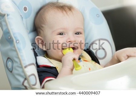 Portrait of beautiful 9 month baby boy playing with spoon while eating - stock photo