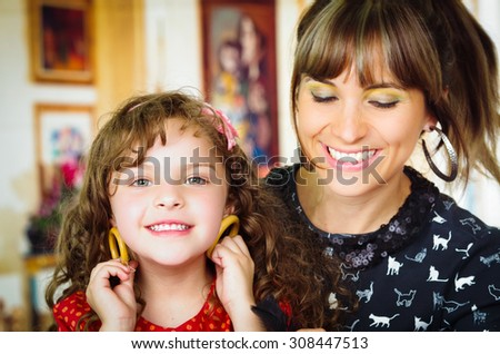 Portrait of beautiful mother and daughter playing with earrings - stock photo