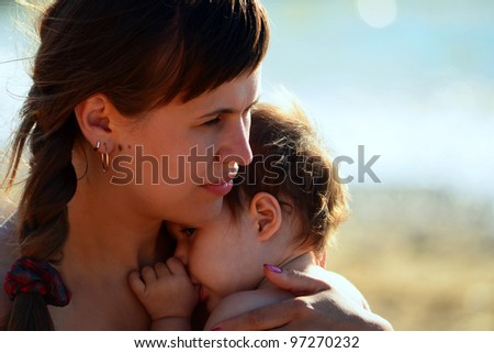 portrait of beautiful mother and sweet child outdoor - stock photo