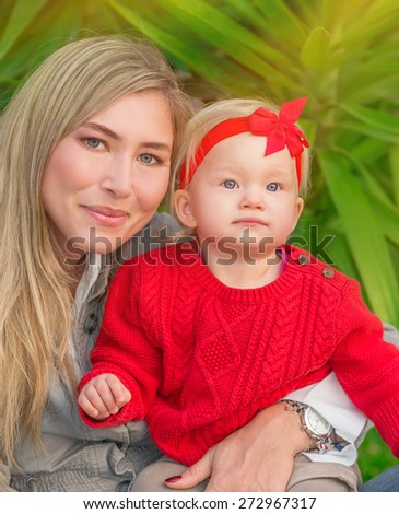 Portrait of beautiful mother with cute little daughter having fun in fresh green park, happy young family enjoying spring season - stock photo