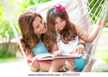 Portrait of beautiful mother with cute little daughter sitting on backyard in hammock and reading funny story, happy family life - stock photo