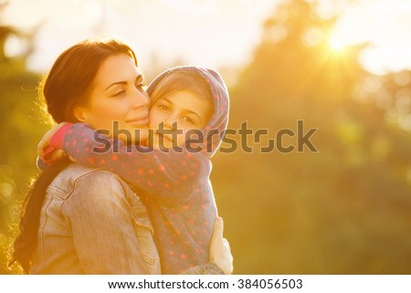 Portrait of beautiful mother with love hugging her precious daughter in bright yellow sunlight in the park, happy family life - stock photo
