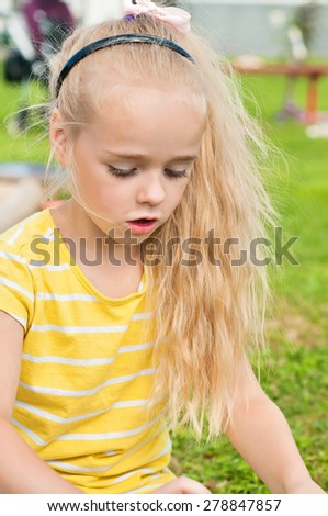 Portrait of beautiful playing little girl with long hair on the playground - stock photo