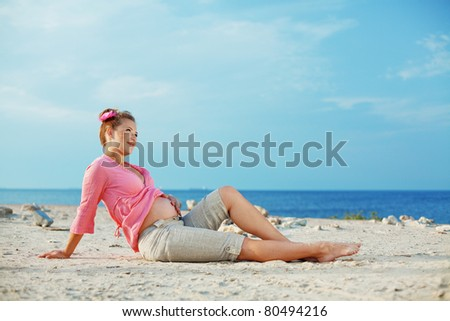 Portrait of beautiful pregnant woman at beach - stock photo