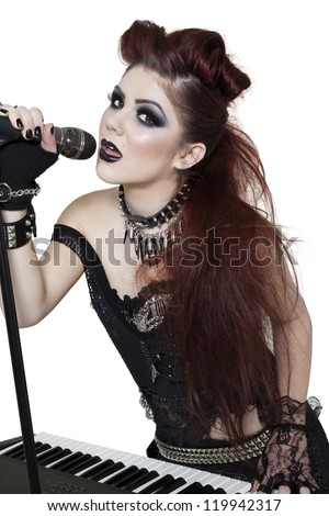 Portrait of beautiful punk woman playing piano while singing with microphone over white background - stock photo