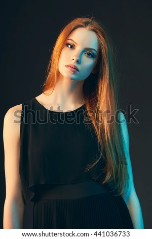 Portrait of beautiful red haired fashion model girl with long hair in black dress over dark background, in colorful lighting, tonned image - stock photo