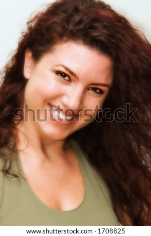 Portrait of beautiful redhead woman smiling. Soft focus. Eyes and smile kept sharp. - stock photo