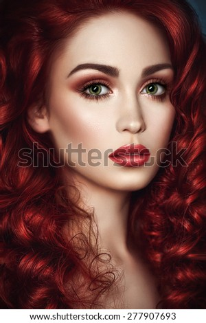 Portrait of beautiful redhead woman with wavy hair and green eyes looking at camera - stock photo