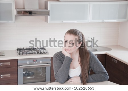 Portrait of beautiful relaxed young woman siting on the kitchen - Indoor - stock photo