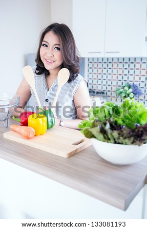 Portrait of beautiful relaxed young woman standing at the kitchen counter - stock photo