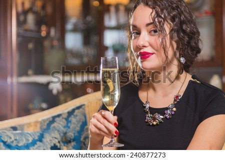 Portrait of beautiful romantic brunette with a champagne glass. Professional make-up on a beautiful woman. A girl sits in a beautiful interior and mysterious looking. Drink, beautiful girl portrait. - stock photo