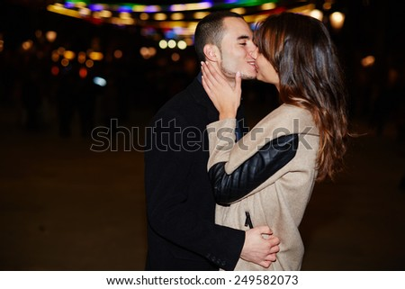 Portrait of beautiful romantic couple embracing at outdoor night event with beautiful lights on background - stock photo
