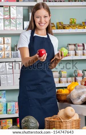 Portrait of beautiful saleswoman holding apples in supermarket - stock photo