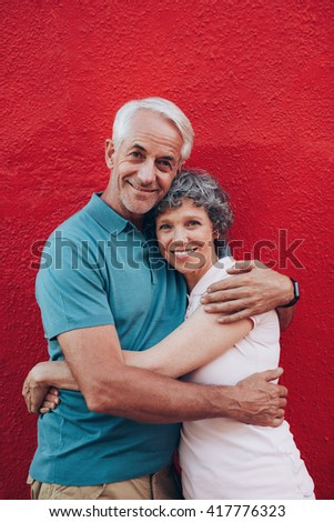 Portrait of beautiful senior couple embracing against red background. Loving mature couple standing together. - stock photo