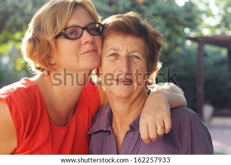 Portrait of beautiful senior woman and her adult daughter - stock photo
