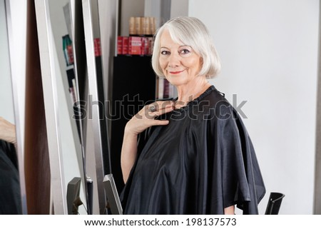 Portrait of beautiful senior woman in apron waiting for hairdresser at salon - stock photo
