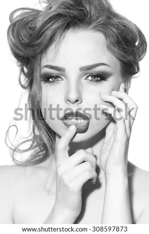 Portrait of beautiful sensual undressed woman with soft lips and curly hair holding finger near lips looking forward standing on studio background black and white, vertical picture - stock photo