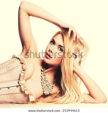 Portrait of beautiful sensual woman with blonde long hair lying at the floor - isolated on white. - stock photo