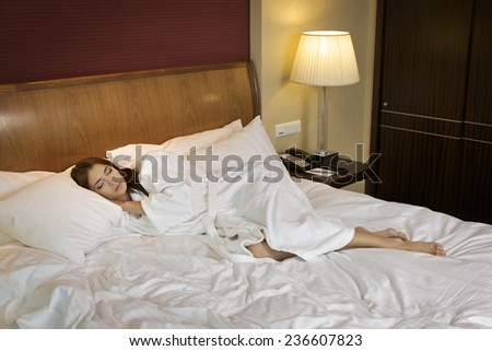 Portrait of beautiful sensuality and attractive young adult brunette woman sleeping in the white bed - stock photo