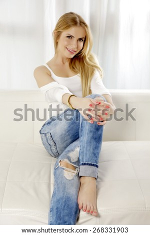 Portrait of beautiful sensuality sexy and attractive young adult smile pretty blonde woman posing in blue jeans and white shirt sweater on the white couch sofa - stock photo